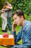 Close up of sad man wearing a jean jacket and black pants sitting in the ground holding a gift in his hands, with a. Blurred couple behind embracing each other Royalty Free Stock Photography