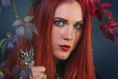 Close up of a sad and melancholic beautiful red head woman among the colorful autumn leaves stock photo