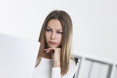 Close up of sad woman in office looking at screen Royalty Free Stock Photo