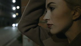 Close up of sad young woman in coat sitting near the wall at night. Slow motion. stock footage