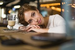 Close up of sad young woman deep in thought outdoors. Portrait of young cute elegant woman sitting outdoor in a cafe in stock photo