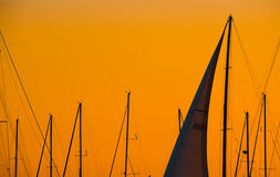 Close up of a sail silhouette under an orange sky at dusk Royalty Free Stock Image