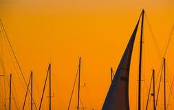 Close up of a sail silhouette under an orange sky at dusk. Close up of a sail silhouette under an orange sky at sunset. Shot in Alghero, Sardinia Royalty Free Stock Image