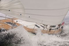Sailing Boat Yacht in Rough Sea Waves. Close up of sailing boat, sail boat or yacht crashing through waves in a rough sea Royalty Free Stock Images