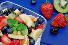 Salad with fresh fruits and berries in a bowl on blue wooden table stock photos