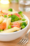 Close-up salad with pasta, smoked salmon, broccoli, green peas Royalty Free Stock Photo