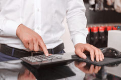 Close up of sales assistant using calculator Royalty Free Stock Photography