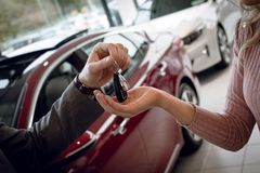 Close up of salesman giving car keys to female customer. While standing in showroom Stock Image