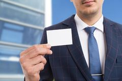Close-up of salesman holding empty white card. As advertisement concept on outdoor background stock images