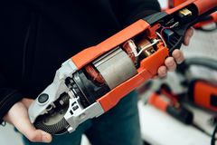 Close up. Salesman is posing with new disc grinder in power tools store. royalty free stock images
