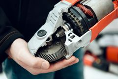 Close up. Salesman is posing with new disc grinder in power tools store. Close up. Salesman is posing with new disc grinder in aisle of power tools store stock photo