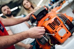 Close up. Salesman is showing couple of clients new leaf blower in power tools store. Close up. Salesman in red shirt and baseball cap is showing couple of royalty free stock photography