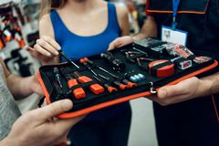 Close up. Salesman is showing couple of clients new toolbox in power tools store. Close up. Salesman in red shirt and baseball cap is showing couple of clients Royalty Free Stock Image