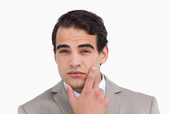 Close up of salesman in thinkers pose. Against a white background Stock Photography