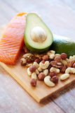 Close up of salmon, avocado and nuts on table Stock Image