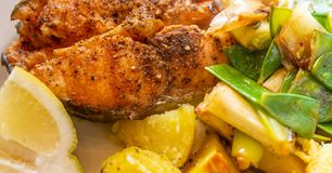 Close-up of salmon cutlet with potatoes on spring onions and sugar snap peas stock images