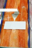 Close up Salmon fillet on ice with white label tag at fish marke. T. Image of salmon texture detail in market background. Raw salmon portion on display at market Stock Photo
