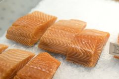 Close up of salmon fillets spread over ice on a fish monger's. Close up of salmon fillets spread over ice on a fish monger's market stall in England Royalty Free Stock Photos