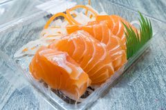 Close Up of salmon raw sashimi pack in clear plastic box on wooden table. Royalty Free Stock Photography