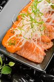 Close up on salmon sashimi. On black plate. Fish delicacy completed with daikon and spring onion. Best Japanese food stock photo