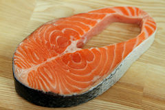 Close-up salmon steak on wooden plate Stock Image