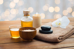 Close up of salt, massage oil and bath stuff. Beauty, spa, body care, natural cosmetics and concept - close up of pink salt with massage oil and bath towel on stock photo