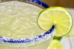 Margarita with lime. Close up of a salted margarita on the rocks with lime slice in a blue rimmed glass royalty free stock image