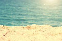 Close up on the sand of a beach, summer background. Close up on the sand of a beach, blue ocean, summer background Stock Photo