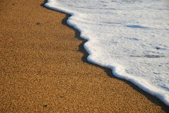 Close-up of sand beach with the foamy wave Royalty Free Stock Photo