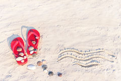 Close up of sand texture with flip flop sandals and shellfishes. Royalty Free Stock Image