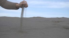 Close up of sand through your fingers. Female hand taking up the sand.  stock video footage