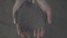 Close up of sand through your fingers. Female hand taking up the sand.  stock video