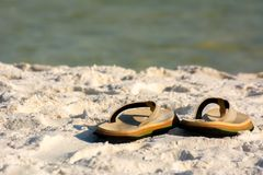 Close Up of Sandals on White Sand on Blur Ocean Water. Destin Beach, Florida. Close Up of Sandals on White Sand on Blur Ocean Water stock images