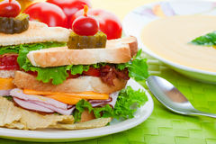 Close up sandwich. Close up of a Cub sandwich on a green place mat with yellow soup Royalty Free Stock Photos
