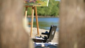 Close-up, a sandy beach by the river, on the sand an easel with a picture is standing, and next to it there is a special. Suitcase with different colors in stock video