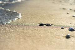 Close up of a sandy beach with a wave coming in stock photo