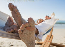 Close up of sandy feet of couple in a hammock. On the beach stock photography