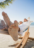 Close up of sandy feet of couple sleeping in a hammock. On the beach Stock Photography