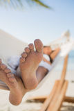 Close up of sandy feet of woman sleeping in a hammock Stock Images