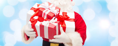 Close up of santa claus with gift box. Christmas, holidays and people concept - close up of santa claus with gift box over blue lights background Royalty Free Stock Photo