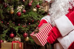 Kind mysterious grandfather putting present box under Christmas tree. Close up of Santa Claus hands laying Christmas gift under the fir-tree. He is wearing red Stock Images