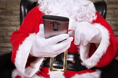 Close up on Santa Claus is holding and touching smartphone. Real close up Royalty Free Stock Images