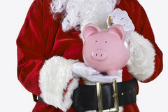 Close Up Of Santa Claus Putting Coin Into Piggy Bank Royalty Free Stock Photo