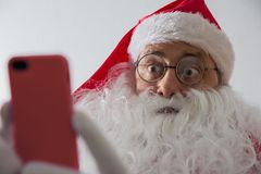 Close up of Santa Claus holding smartphone and looking surprised. Close up of Santa Claus or Saint Nicholas holding smartphone and looking surprised at screen royalty free stock photos