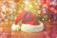 Close up of santa hat on wooden table over lights Royalty Free Stock Image