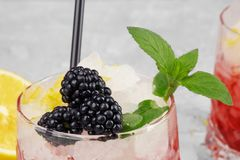 Closeup of a glass of fruit juice, succulent blackberries, green sappy leaves of mint on a light blurred background. Close-up of sappy fresh blackberries in a Stock Image