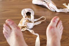 Close up of pointe shoes near defocused tired feet of ballet dancer royalty free stock photography