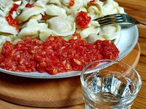 Sauce of horseradish, garlic and tomatoes against the background of Siberian Russian pelmeni and vodka. Natural food, appetiz. Closeup - a sauce of horseradish royalty free stock image