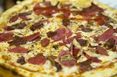 Close-up of sausage, bacon, ham, yellow cheese and mushroom pizza. On hot pizza spices scattered royalty free stock photos