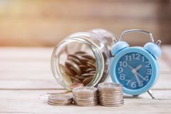 Close up saving money into a glass jar and alarm clock for cash royalty free stock images